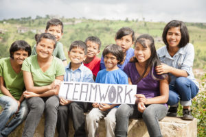 "Multi-ethnic and mixed aged group of children holding a white, sign outdoors that reads ""Teamwork"". The group is of Latin, Asian, and Indian descent. They are sitting outdoors with a view of their countryside behind them. Collaboration, volunteerism themes."